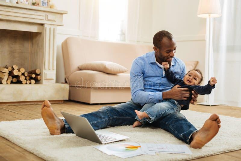 使他的小儿子发笑的有同情心的父亲 免版税库存图片