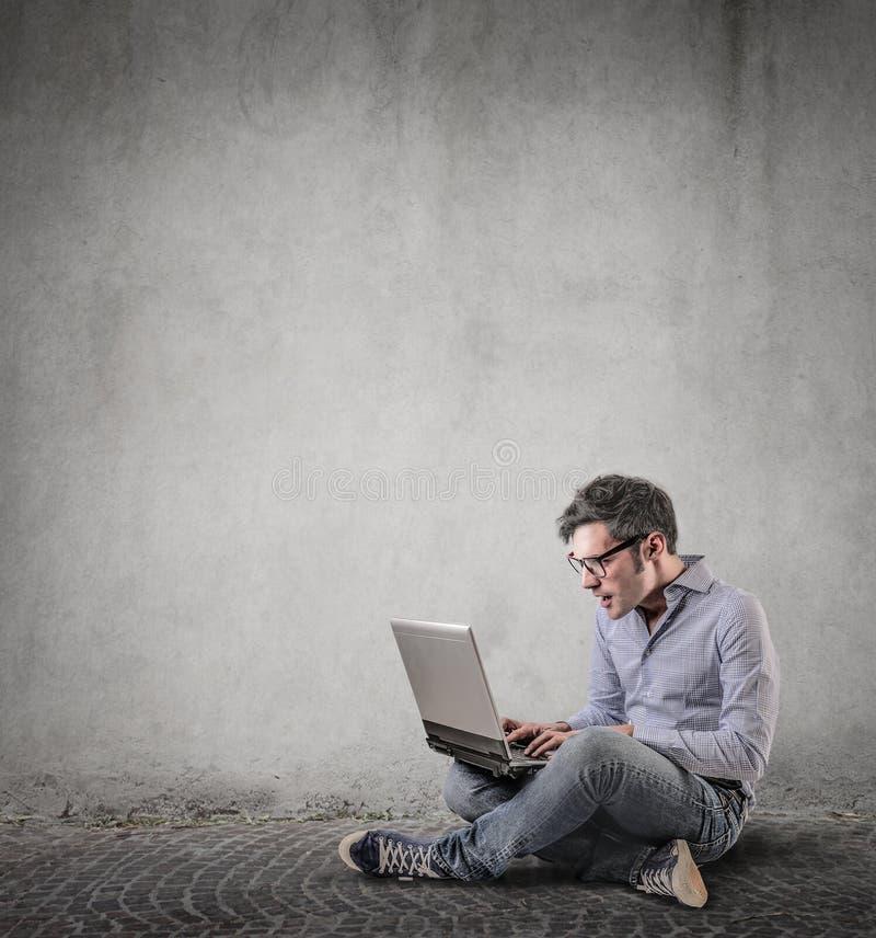 使使用他的膝上型计算机惊奇 免版税库存照片