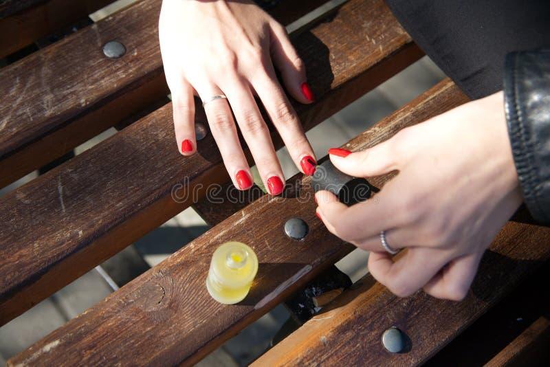 使修指甲室外一个女孩的手 免版税图库摄影