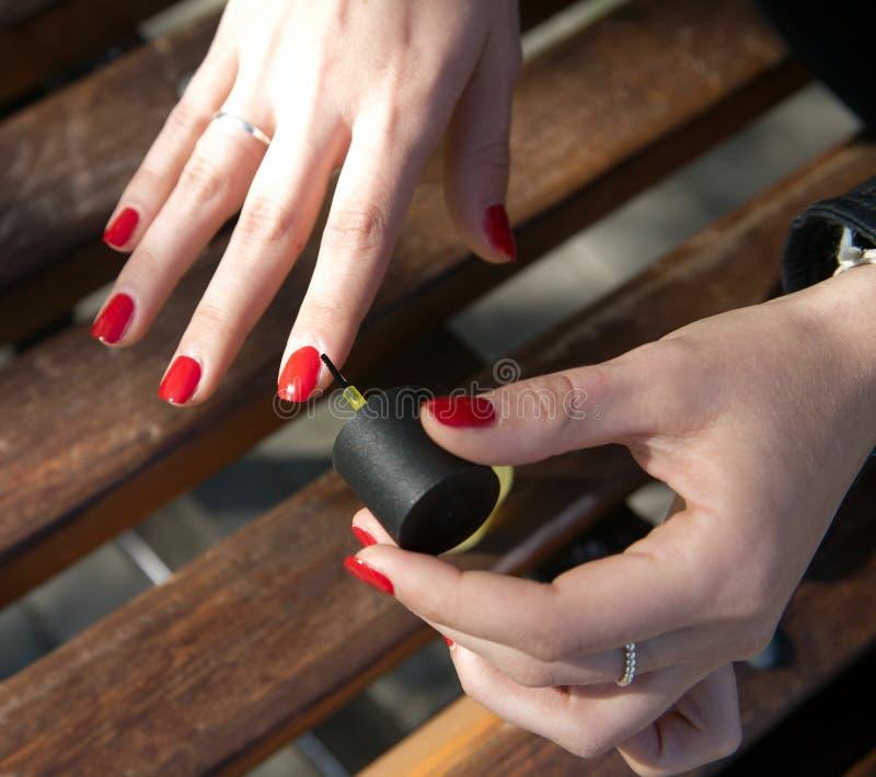 使修指甲室外一个女孩的手 图库摄影
