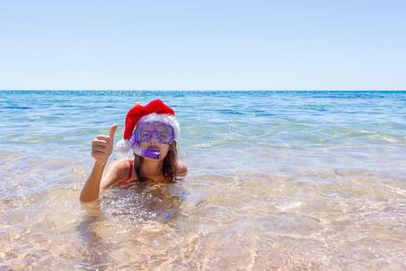 使假期戴一个面具管和圣诞节帽子游泳的乐趣妇女靠岸在海洋水中 一个女孩的特写镜头画象她的tra的 免版税库存图片