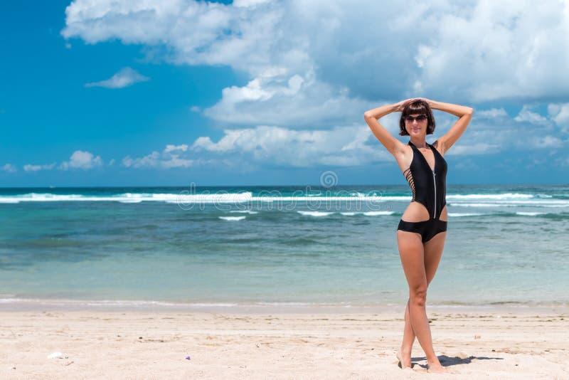 使假期靠岸 享受晴天的愉快的妇女在海滩 打开胳膊、自由、幸福和极乐 热带概念 库存图片