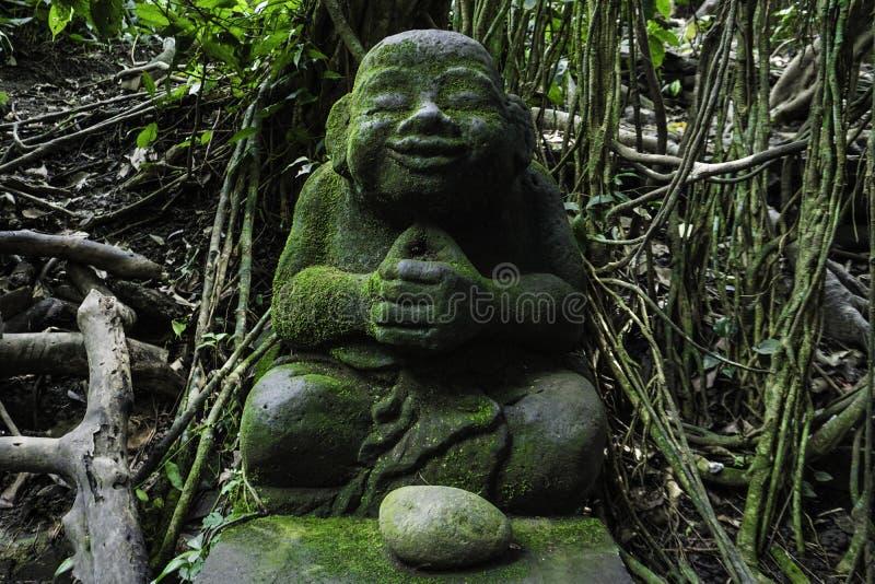 使变冷的菩萨雕象以绿色,巴厘岛猴子森林 库存照片
