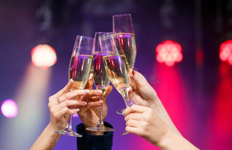 使叮当响的杯香槟在手上在明亮的光背景 库存图片