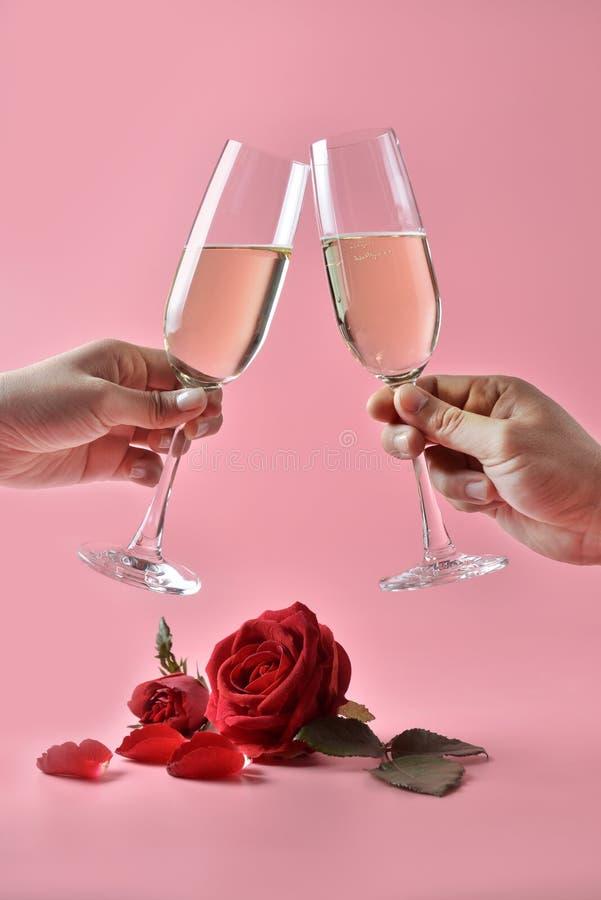 使叮当响的杯香槟在手上,有在底部的红色玫瑰的在桃红色背景 华伦泰` s天的概念 免版税库存图片