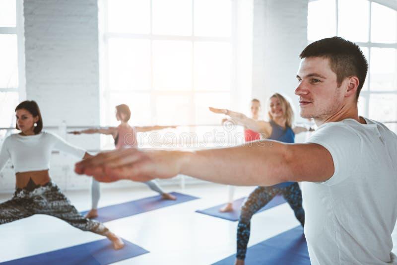 使和做在类的小组男人和妇女健身训练兴奋 年轻活跃人民一起做着瑜伽 免版税库存图片