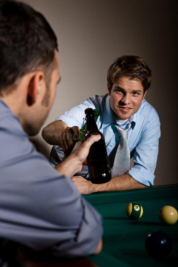 使啤酒瓶叮当响的朋友在落袋球球台 库存图片