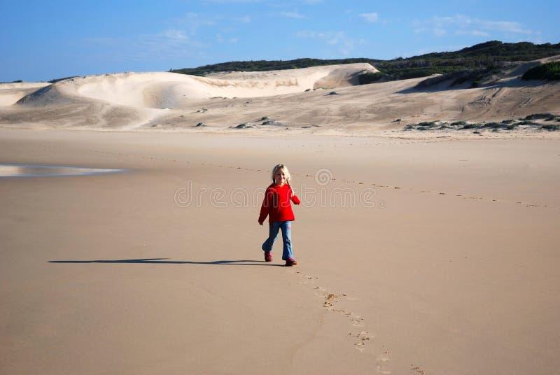使女孩靠岸走的一点 免版税图库摄影