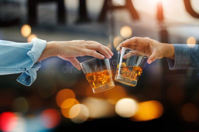 使威士忌酒玻璃叮当响的两个人特写镜头在工作以后一起喝酒精饮料,当在酒吧柜台在客栈时 免版税库存照片
