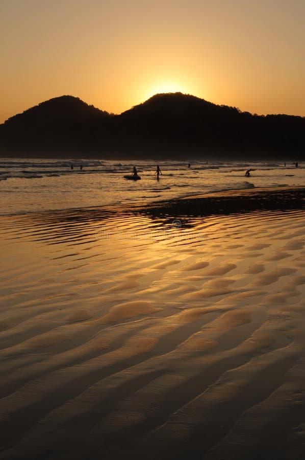 使孩子热带反映的日落靠岸 库存照片
