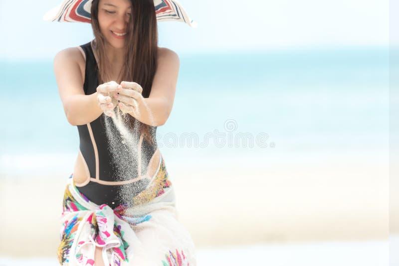 使布赖顿椅子日甲板英国节假日懒人海边有风夏天的星期日靠岸 和播放沙子的生活方式微笑的亚裔妇女佩带的比基尼泳装时尚夏天旅行坐含沙海洋 库存图片