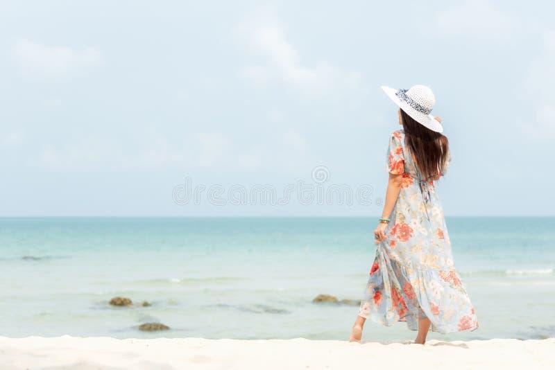 使布赖顿椅子日甲板英国节假日懒人海边有风夏天的星期日靠岸 站立在含沙海洋海滩的生活方式妇女佩带的时尚夏天旅行 愉快的妇女享用和放松vaca 免版税图库摄影