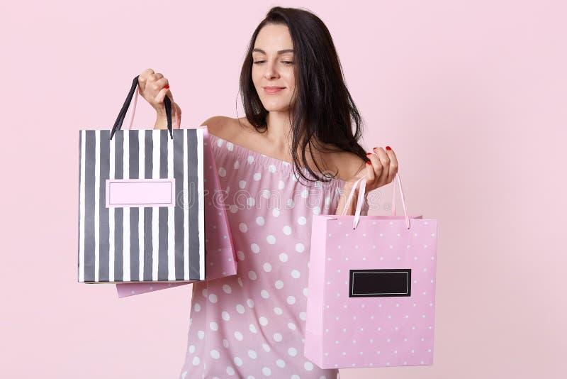 使年轻深色的妇女佩带的圆点礼服惊奇,摆在与购物带来和看的图象下来与沉思脸面护理 图库摄影