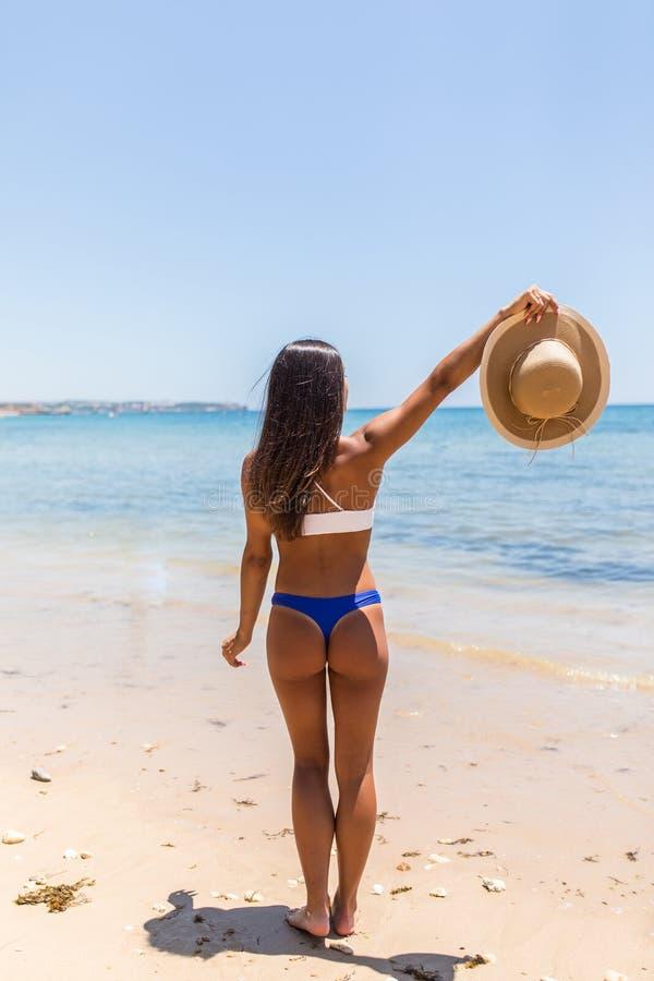 使愉快的自由概念的暑假妇女靠岸与在幸福举的胳膊 拉丁性感的妇女佩带的白色比基尼泳装与 图库摄影