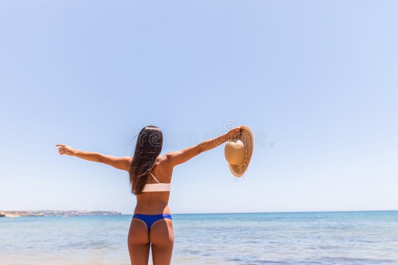 使愉快的自由概念的暑假妇女靠岸与在幸福举的胳膊 拉丁性感的妇女佩带的白色比基尼泳装与 库存照片