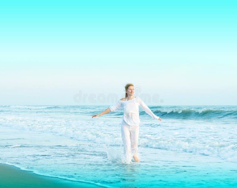 使愉快的跳的妇女年轻人靠岸 图库摄影