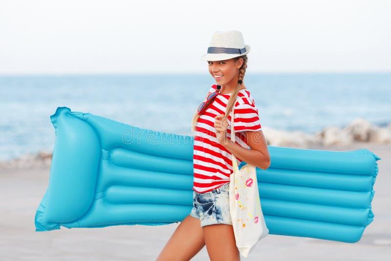 使有蓝色床垫的妇女愉快和佩带的海滩帽子靠岸获得夏天乐趣在旅行假日假期时
