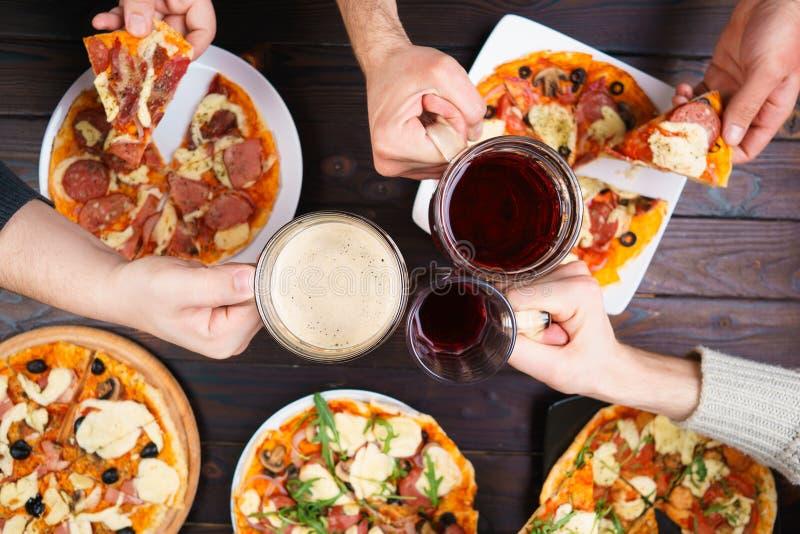 使杯子叮当响用啤酒和吃薄饼的朋友 在ma的顶视图 库存图片