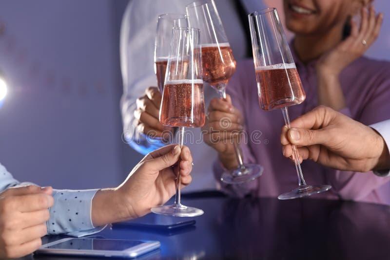使杯香槟叮当响的朋友在桌上在餐馆 免版税库存照片