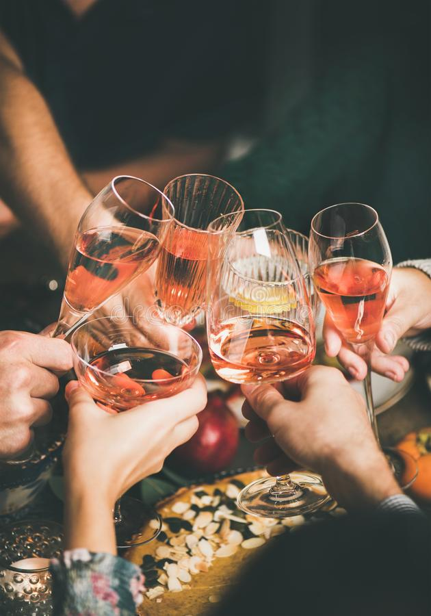 使玻璃叮当响用玫瑰酒红色的朋友在圣诞节桌上 库存图片