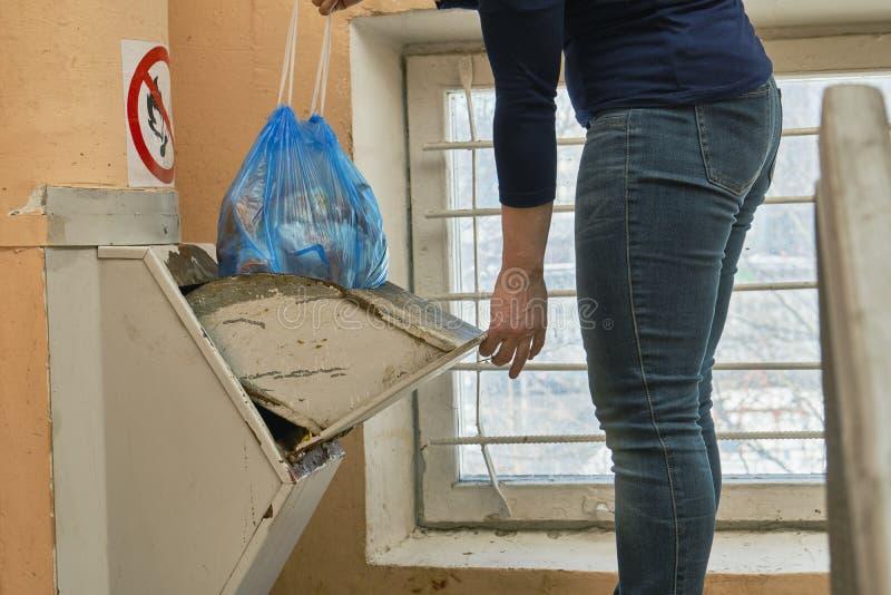 使用一个家庭垃圾滑道,丢掉垃圾的妇女在垃圾袋包装了 免版税库存照片