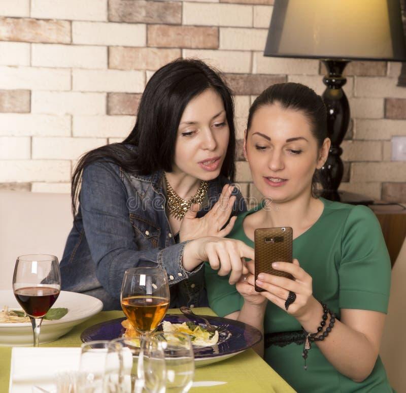 使用一个巧妙的电话的两名妇女 免版税库存图片