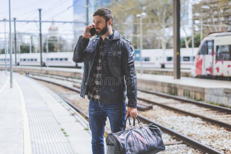 使用一个巧妙的电话的可爱的有胡子的人在他的手站立与旅行袋子在等待火车的平台 免版税库存照片