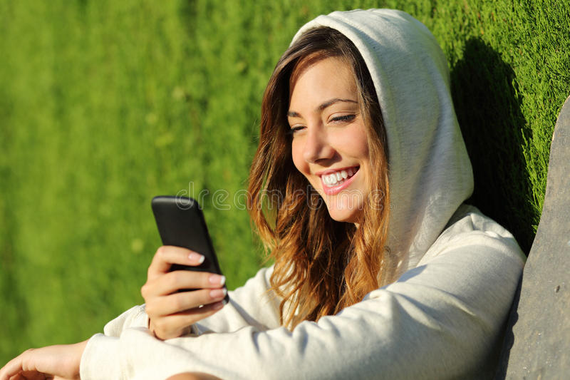 使用一个巧妙的电话的现代少年女孩在公园 免版税图库摄影