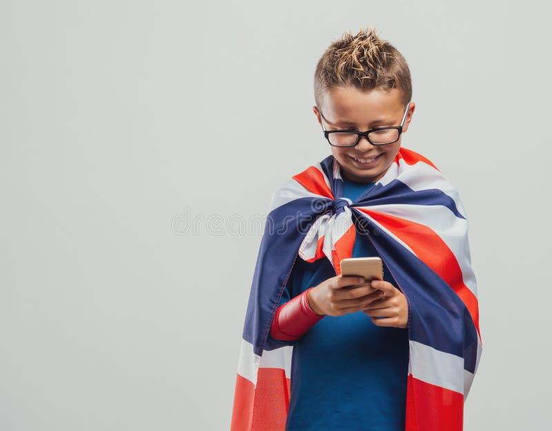 使用一个巧妙的电话的滑稽的英国超级英雄 免版税图库摄影