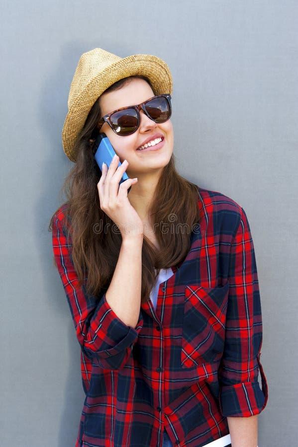 使用一个巧妙的电话,在墙壁的片剂的年轻愉快的青少年的女孩在t 免版税库存图片