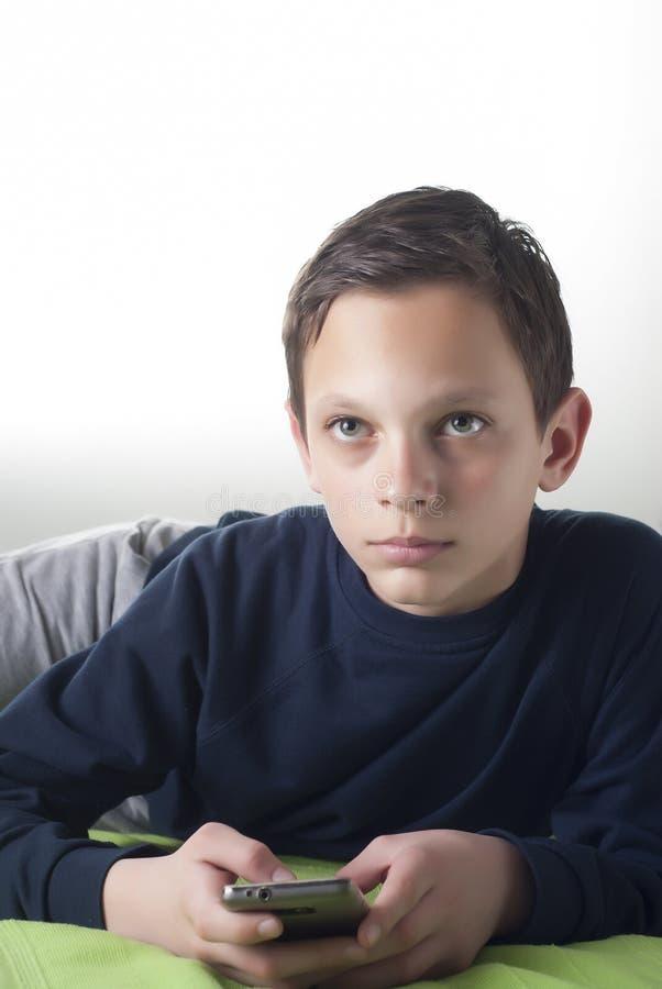 使用一个巧妙的电话的年轻男孩 图库摄影