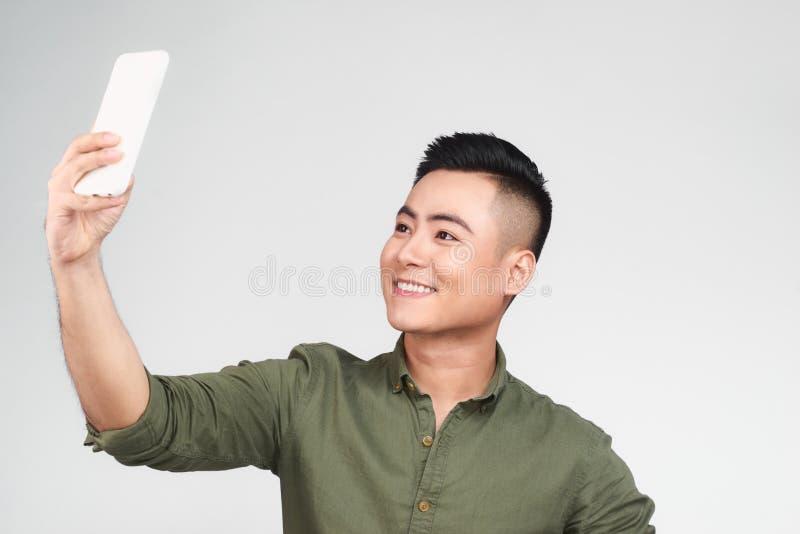 使用一个巧妙的电话,白色衬衣的英俊的人在灰色背景做着selfie,显示好标志并且微笑着, 免版税库存图片