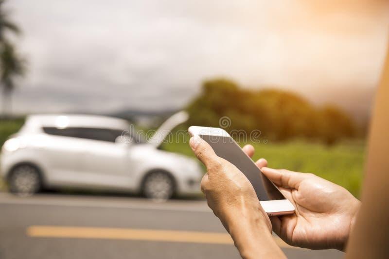 使用一个手机电话汽车修理师,因为汽车是残破的 免版税库存图片