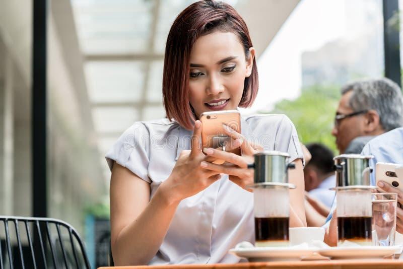 使用一个手机的一名年轻亚裔妇女的画象在咖啡 免版税库存图片