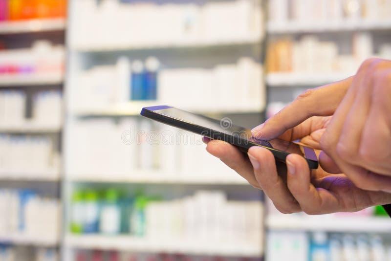 使用一个手机的人在药房 库存图片
