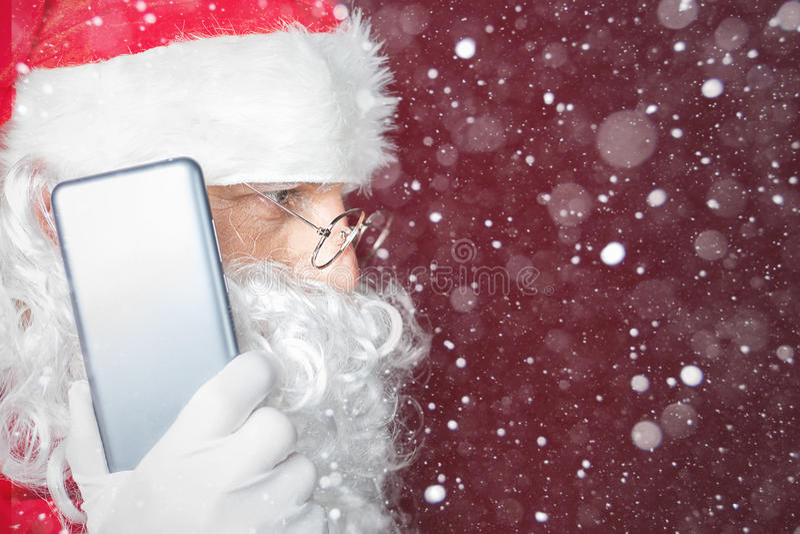 使用一个手机的圣诞老人在圣诞节时间 免版税图库摄影