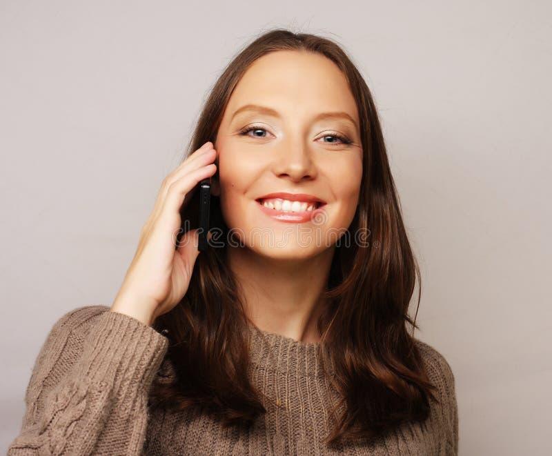 使用一个手机的妇女隔绝在白色背景 图库摄影