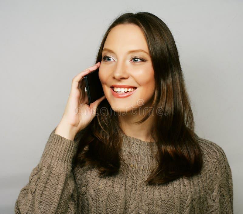 使用一个手机的妇女隔绝在白色背景 免版税图库摄影