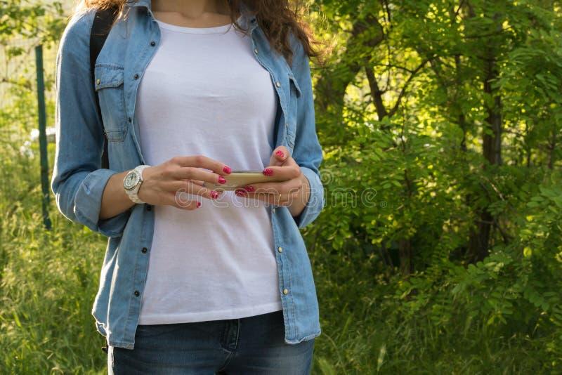 使用一个手机的少妇在与背包的一次远足期间 库存图片