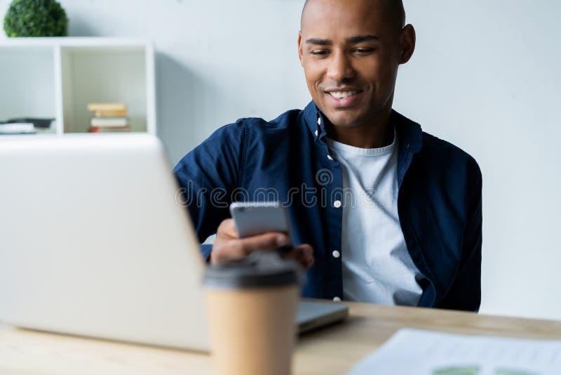 使用一个手机的愉快的非裔美国人的商人在办公室 图库摄影