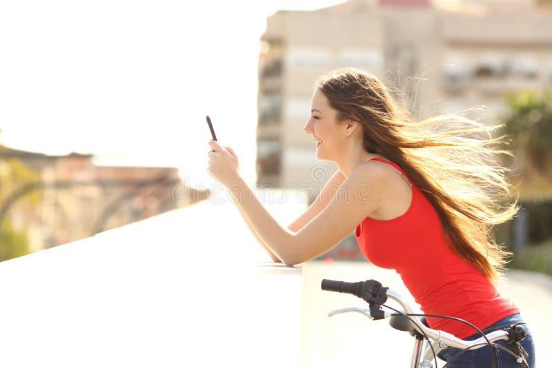 使用一个手机的青少年的女孩的档案在公园 免版税图库摄影
