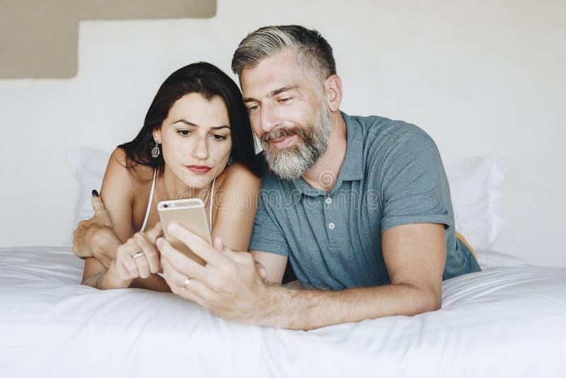 使用一个智能手机的夫妇在床上 免版税库存照片