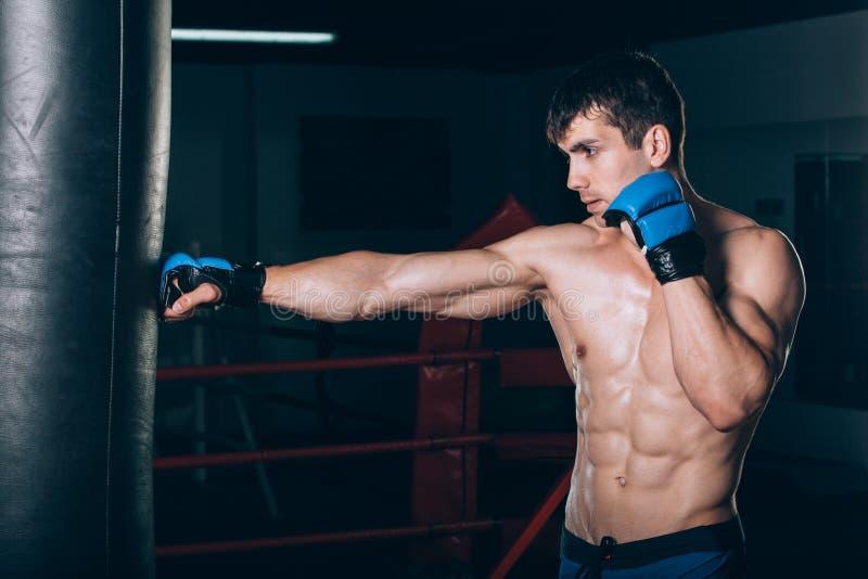 使用一个沙袋的年轻男性拳击手在健身房 免版税库存图片