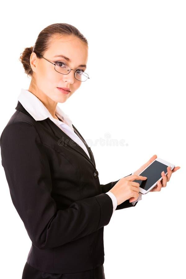 使用一个现代接触电话的严重的女商人 图库摄影