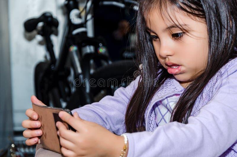 使用一个现代智能手机的逗人喜爱的小女孩 图库摄影