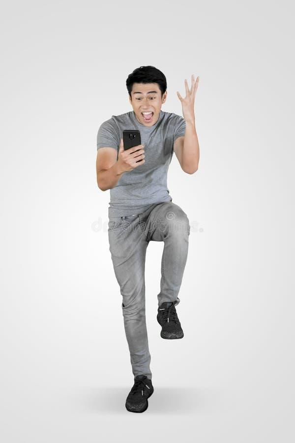 使用一个电话的震惊亚裔人在演播室 库存图片