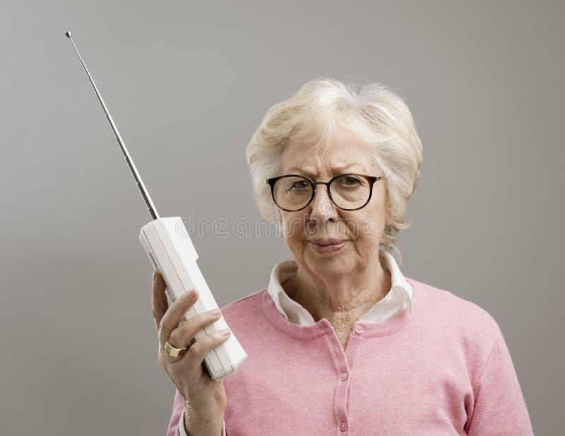 使用一个老电话的沮丧的资深妇女 库存图片