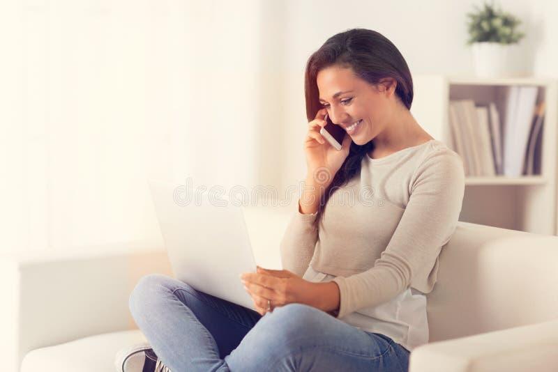 使用一个膝上型计算机和电话在长沙发的愉快的妇女 免版税库存照片