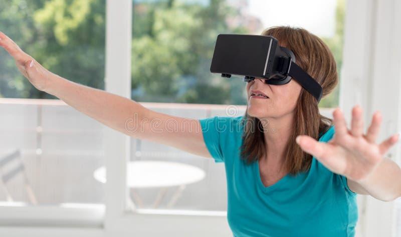 使用一个虚拟现实耳机的妇女 图库摄影