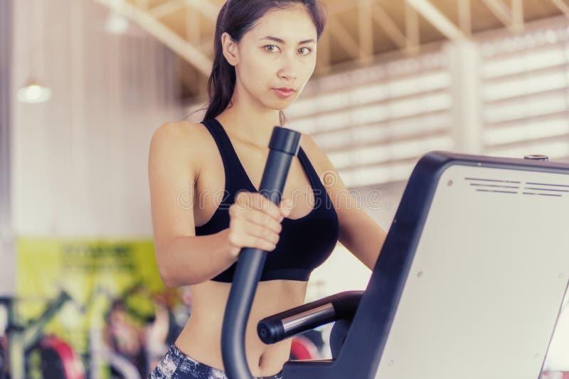 使用一位椭圆教练员的亚洲适合的妇女在健身中心 免版税库存照片